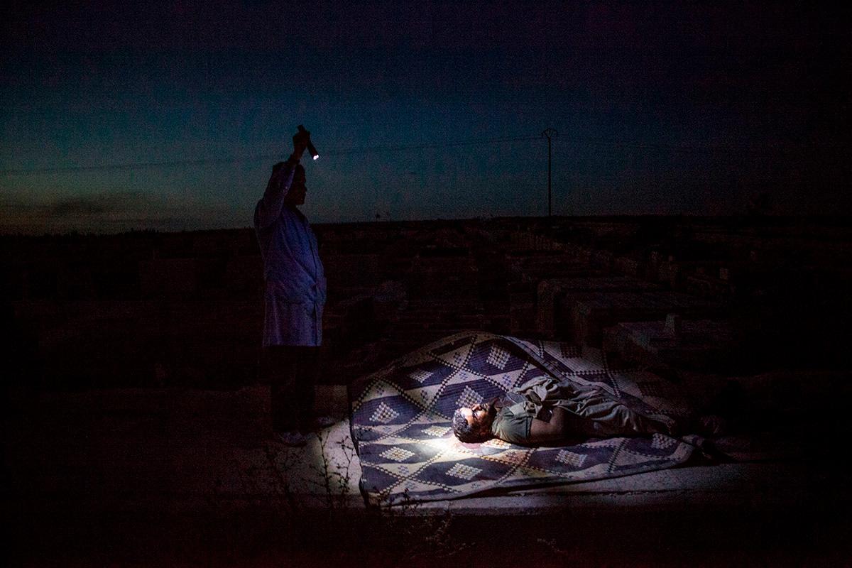 Un rebelde sirio ilumina el cadáver de un combatiente rebelde durante su entierro en Alepo, Siria, 2012. MANU BRAVO